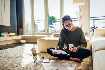 Young person sitting on carpet next to a sofa with paper and mobile phone in hand. There is a laptop and tea cup on the carpet.