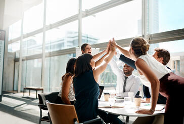 Team of six business people high-fiving while sitting in a light and spacious meeting room