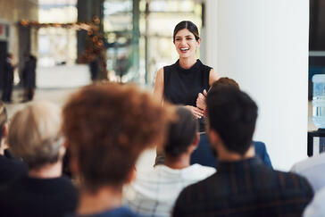 Confident young bookkeeper in black blouse smiling while presenting to a diverse audience during a conference.