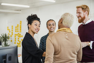 Four colleagues standing in a small group networking while working at an office.