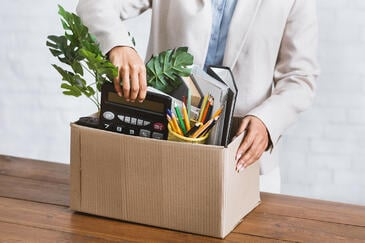 Employee packing a plant, assorted paper, folders, calculator, assorted pens in a box.