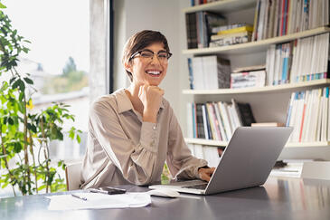 Successful bookkeeper sitting in office and looking at camera, with hand on chin working on computer while smiling